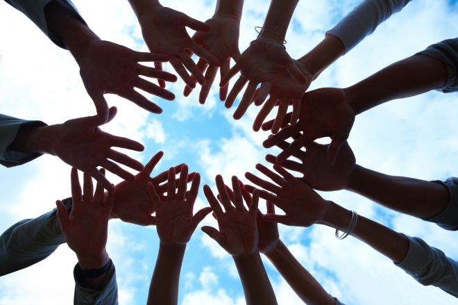 Group of mixed hands showing unity with sky
